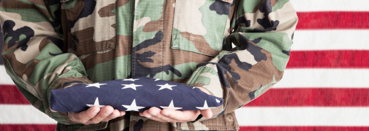 Man in military uniform holding a folded American flag.