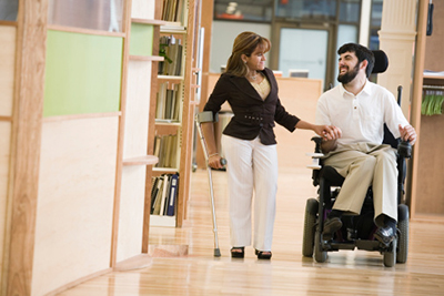 A woman walking down a hall with a man in a powered chair