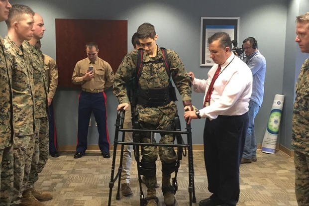 Paralyzed Marine Lance Cpl. Joshua Burch uses an exoskeleton to attend his promotion to corporal at the Hunter Holmes McGuire VA Medical Center in 2016. Photo by Joshua Burch