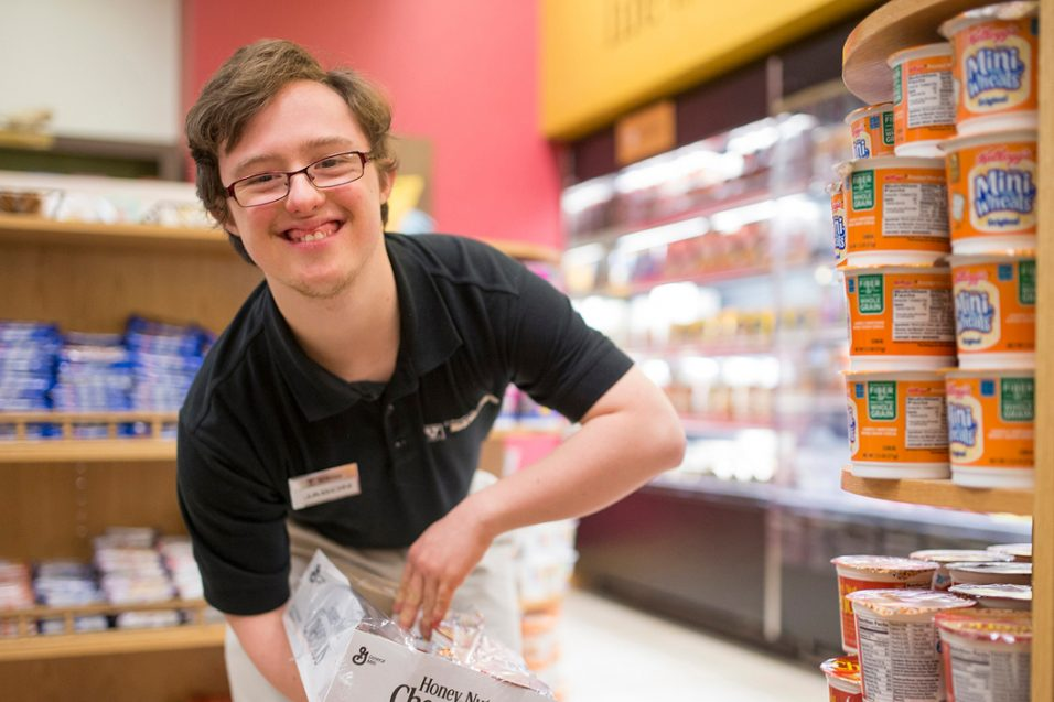 Young man stocking shelves at a grocery store